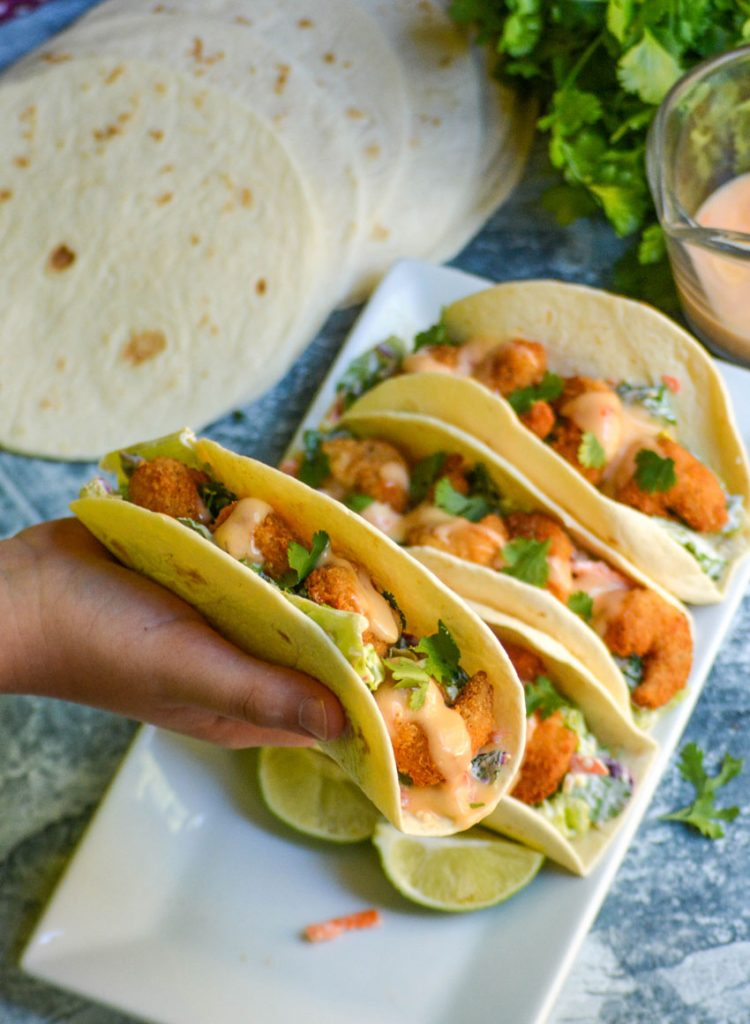 bang bang shrimp tacos lined up on a rectangular white serving platter with a small hand holding one aloft