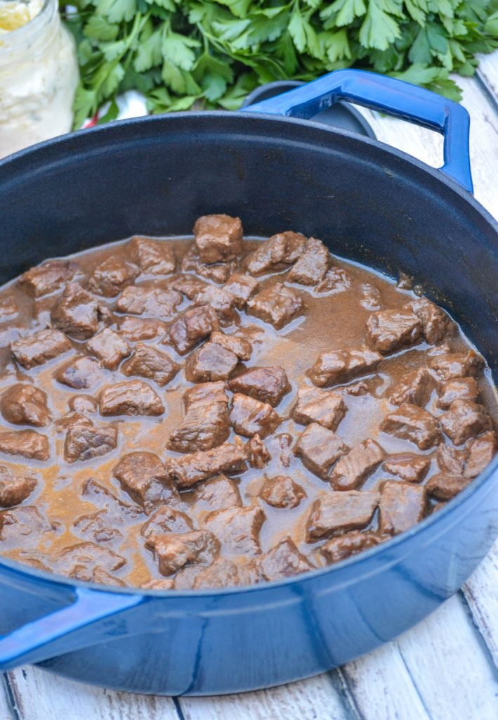 chunks of stew beef in brown gravy in a blue pot