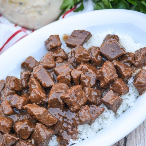 chunks of stew beef in brown gravy over a bed of cooked white rice in a white oval serving dish