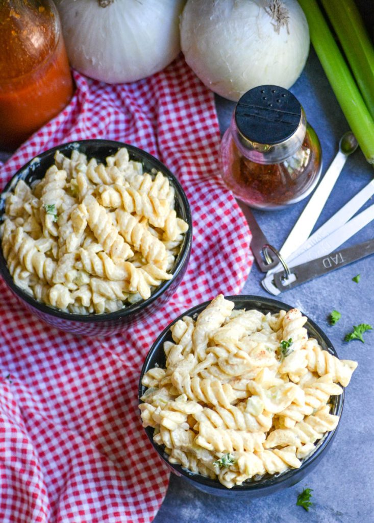 creamy cajun pasta salad shown in two black bowls on top of a red & white checkered cloth napkin