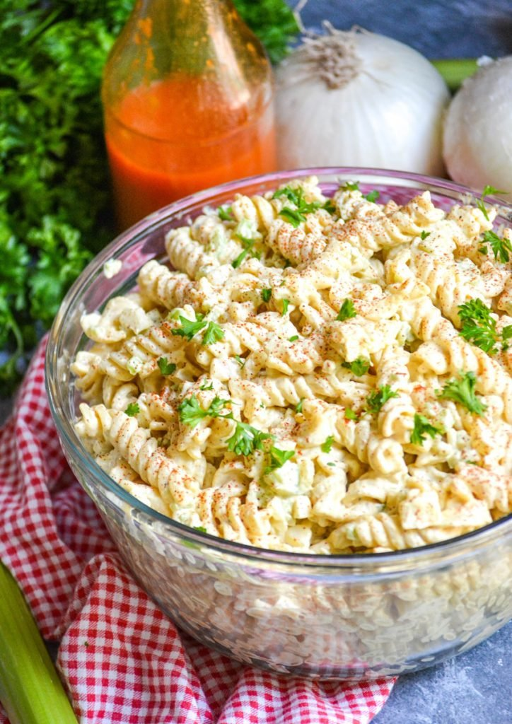 creamy macaroni salad in a glass bowl on top of a red checkered cloth napkin
