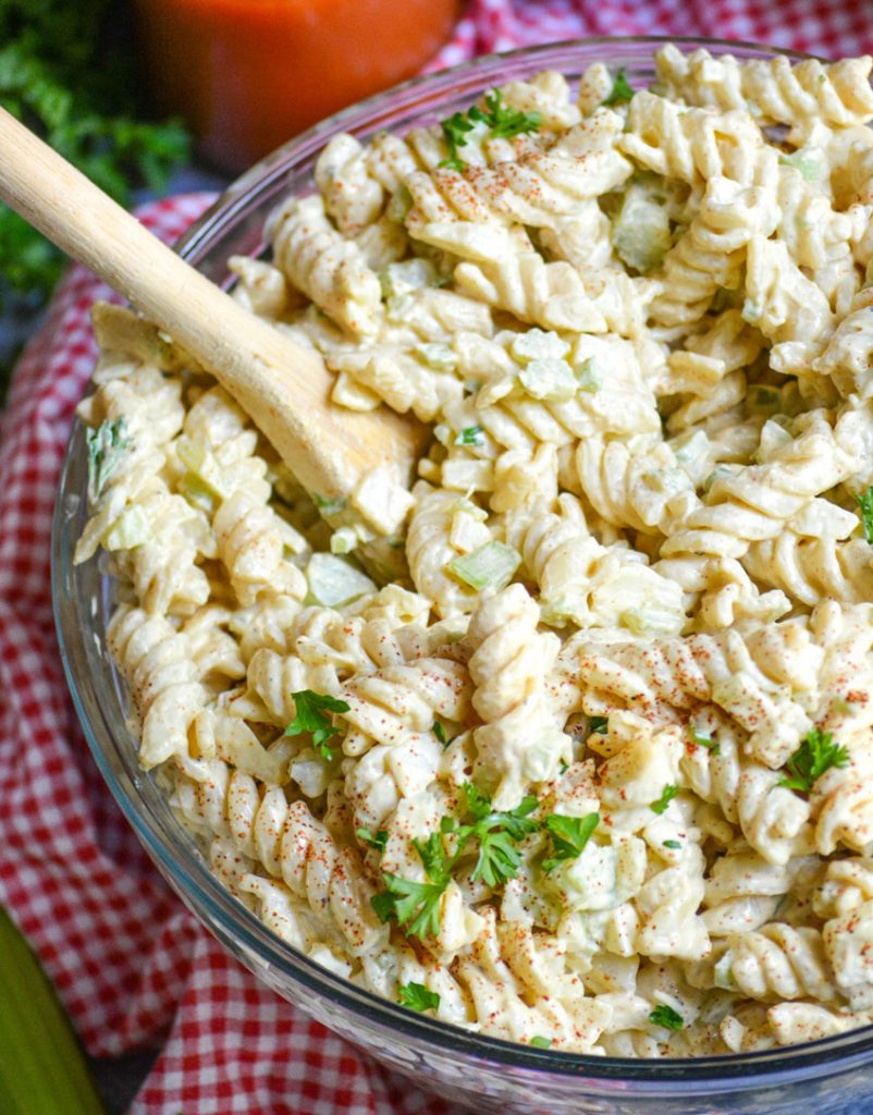 creamy macaroni salad in a glass bowl on top of a red checkered cloth napkin and a wooden spoon taking a scoop out