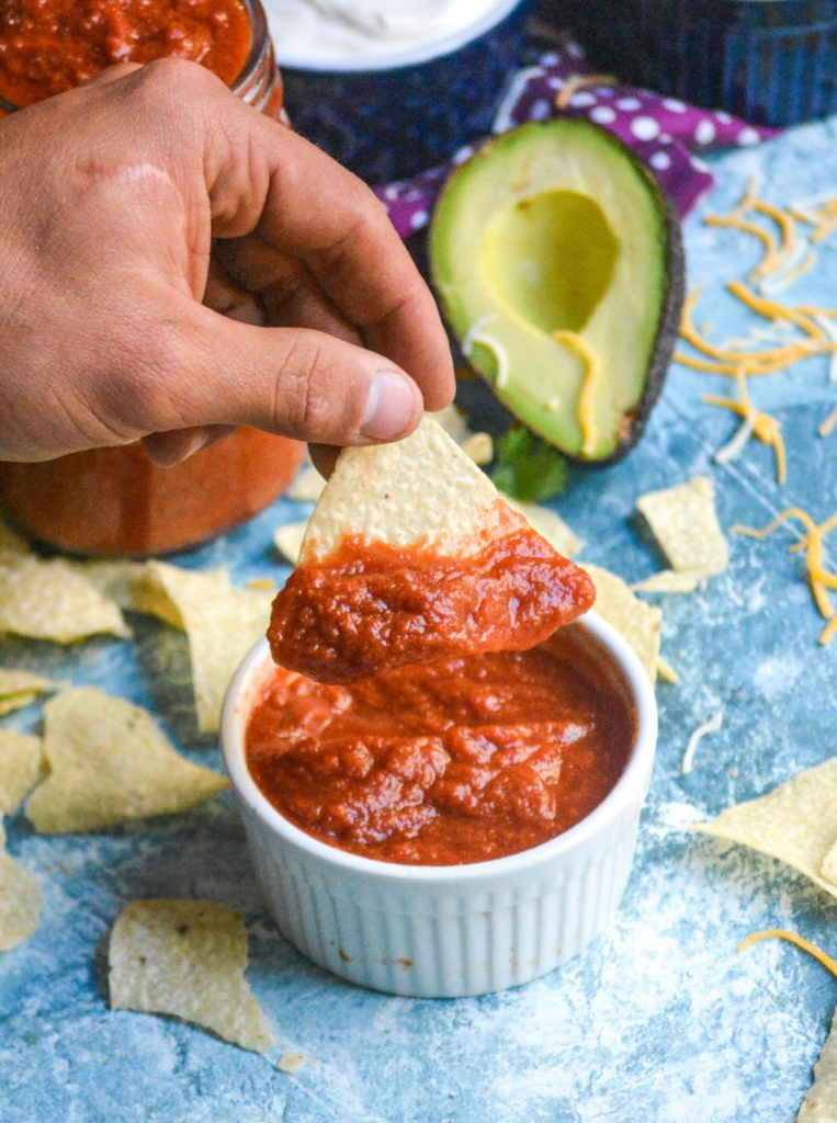 a hand is holding a tortilla chip with homemade taco sauce on it aloft over a white bowl filled with taco sauce on a light blue background
