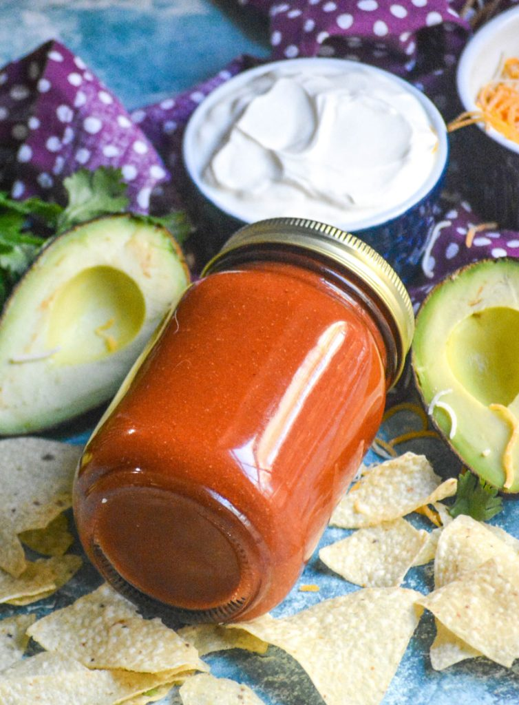 taco sauce in a sealed glass jar laid on it's side and surrounded by chips, a sliced open avocado and a blue bowl filled with fresh sour cream
