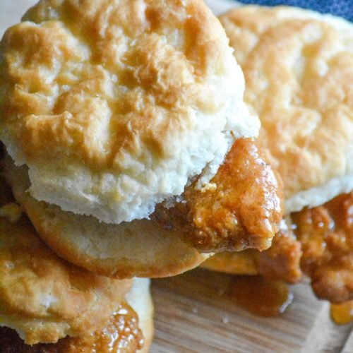 sweet & spicy glazed chicken tenders sandwiched in buttermilk biscuits on a wooden cutting board