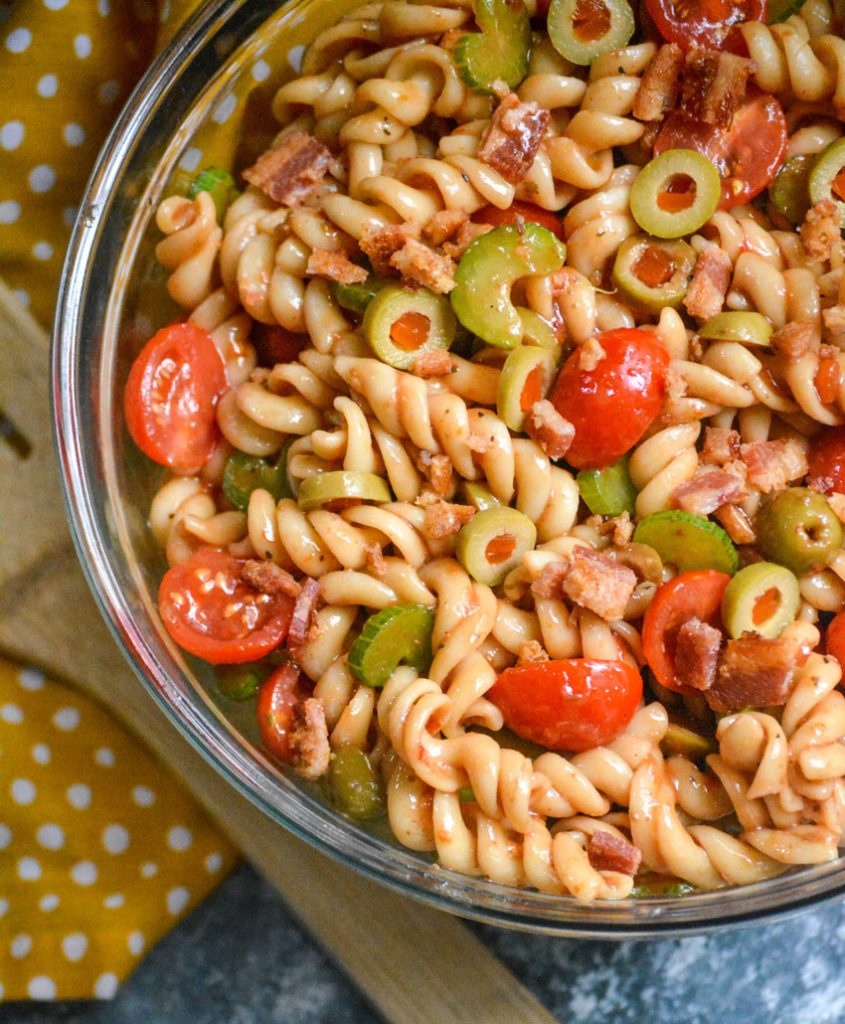 Bloody mary pasta salad in a glass serving bowl on a polka dotted yellow napkin with a wooden spoon for serving