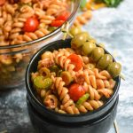bloody mary pasta salad is shown in a small black serving bowl, stacked atop another empty black bowl with a toothpick strung with green Spanish olives as a garnish