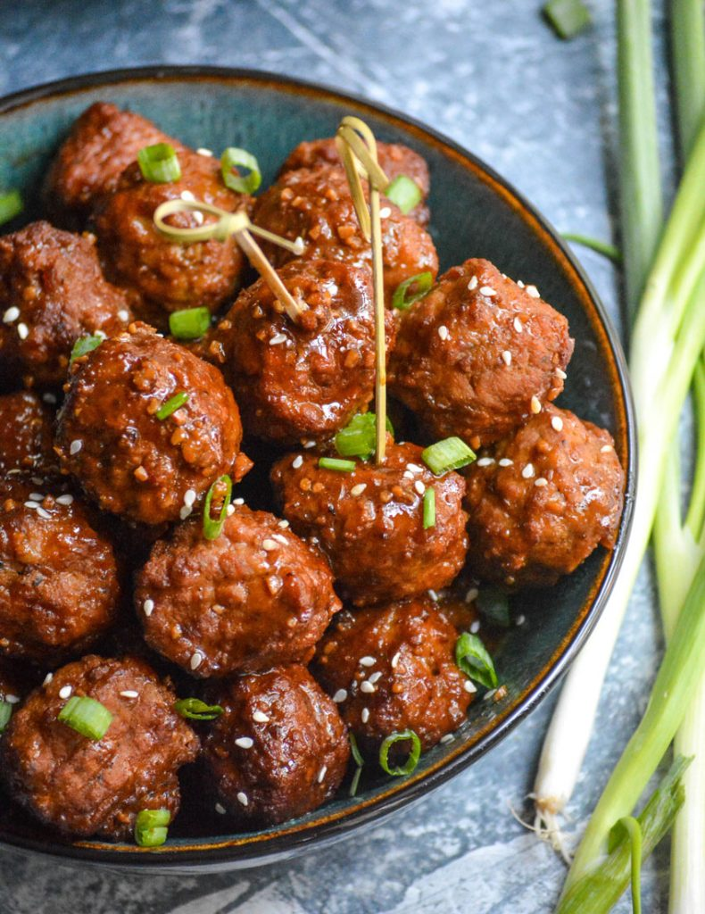 sticky Asian meatballs in a bowl with toothpicks stuck into a few for serving