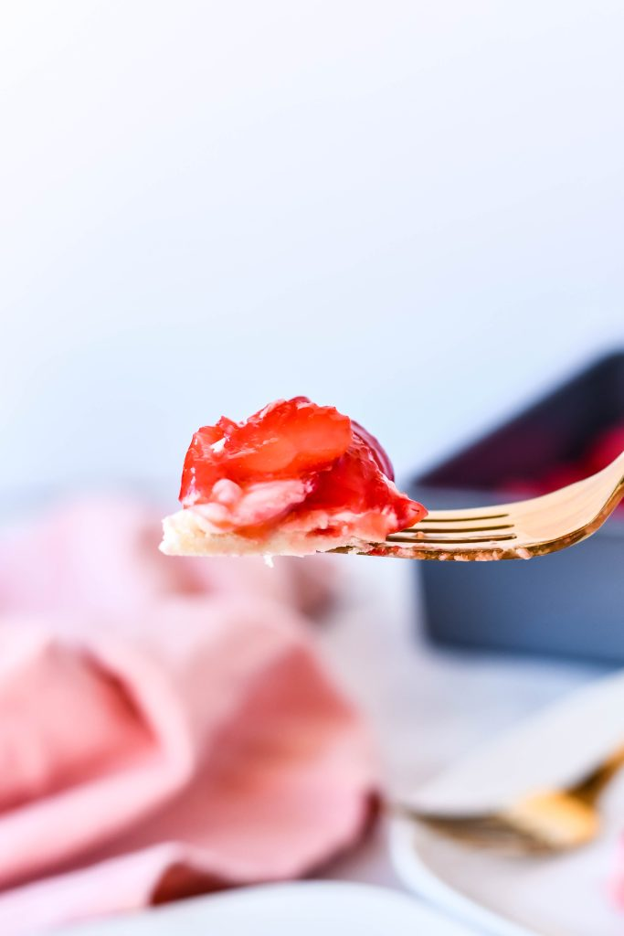 a gold colored fork holding up a bite of strawberry slab pie with a pink cloth napkin in the background