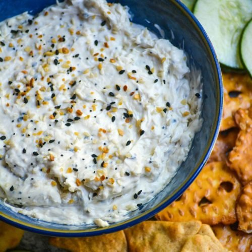 everything bagel dip in blue serving bowl surrounded by crackers, toasts, sliced cucumbers, pretzels, and pita bread