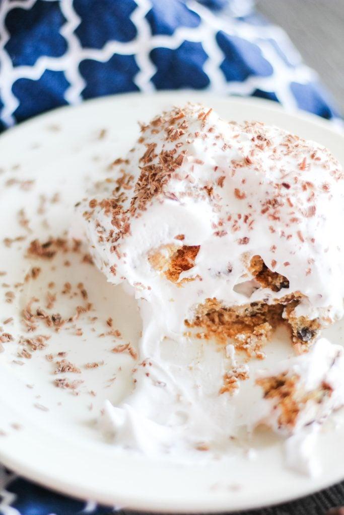 chocolate chip cookie tiramisu on a white dessert plate set on a blue and white dish cloth