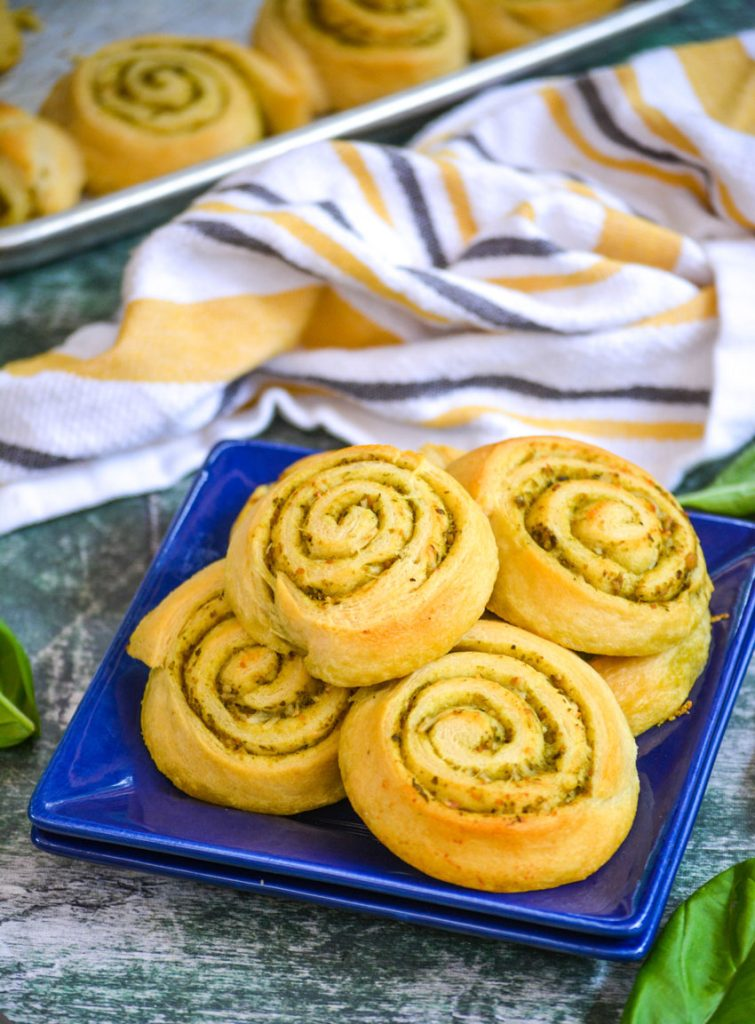 soft buttery pesto lined pinwheels are stacks on a blue appetizer plate with fresh green basil leaves and a striped dishcloth in the backkground