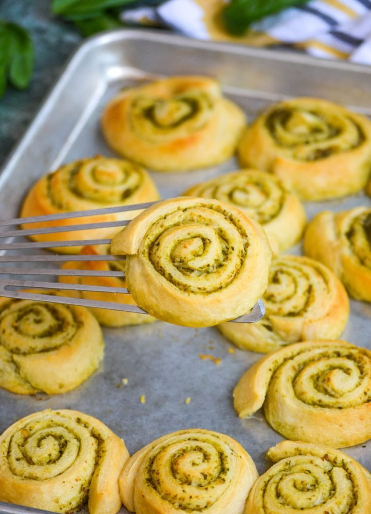 soft buttery pesto lined pinwheels shown on a silver baking tray