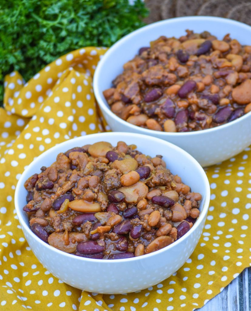 slow cooker cowboy beans in white bowls on a yellow polka dotted cloth napkin