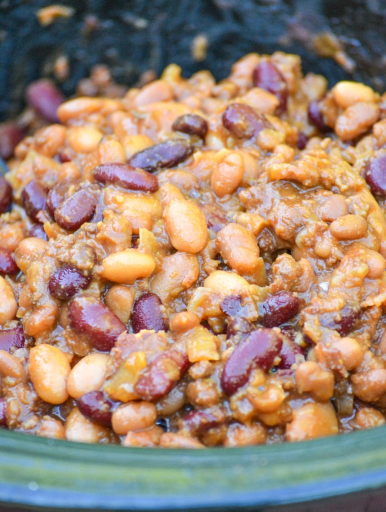 slow cooker cowboy beans in the bowl of crcokpot on a white wooden table