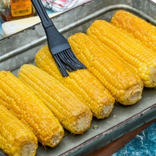 smoked honey butter corn on the cob being rubbed with silicone brush