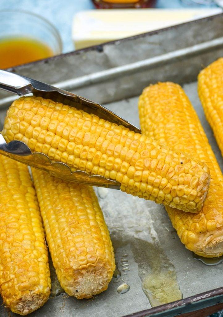 honey glazed smoked corn on the cob held aloft with metal tongs