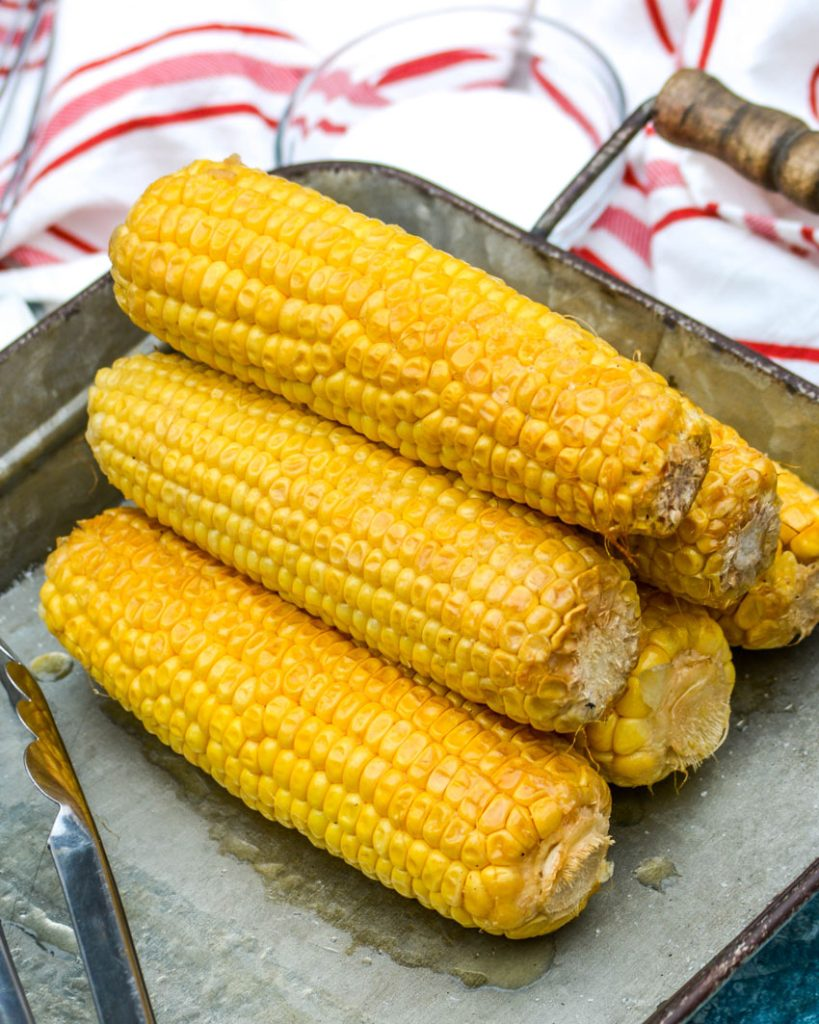 Honey Butter Smoked Corn in a stack on a galvanized metal serving tray