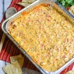 smoked queso dip in an aluminum foil baking pan with fresh tortilla chips and a bunch of cilantro in the background