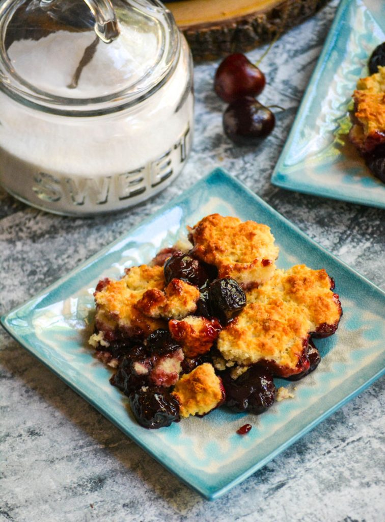 sweet cherry cobbler served on light blue plates with a sugar dish in the background
