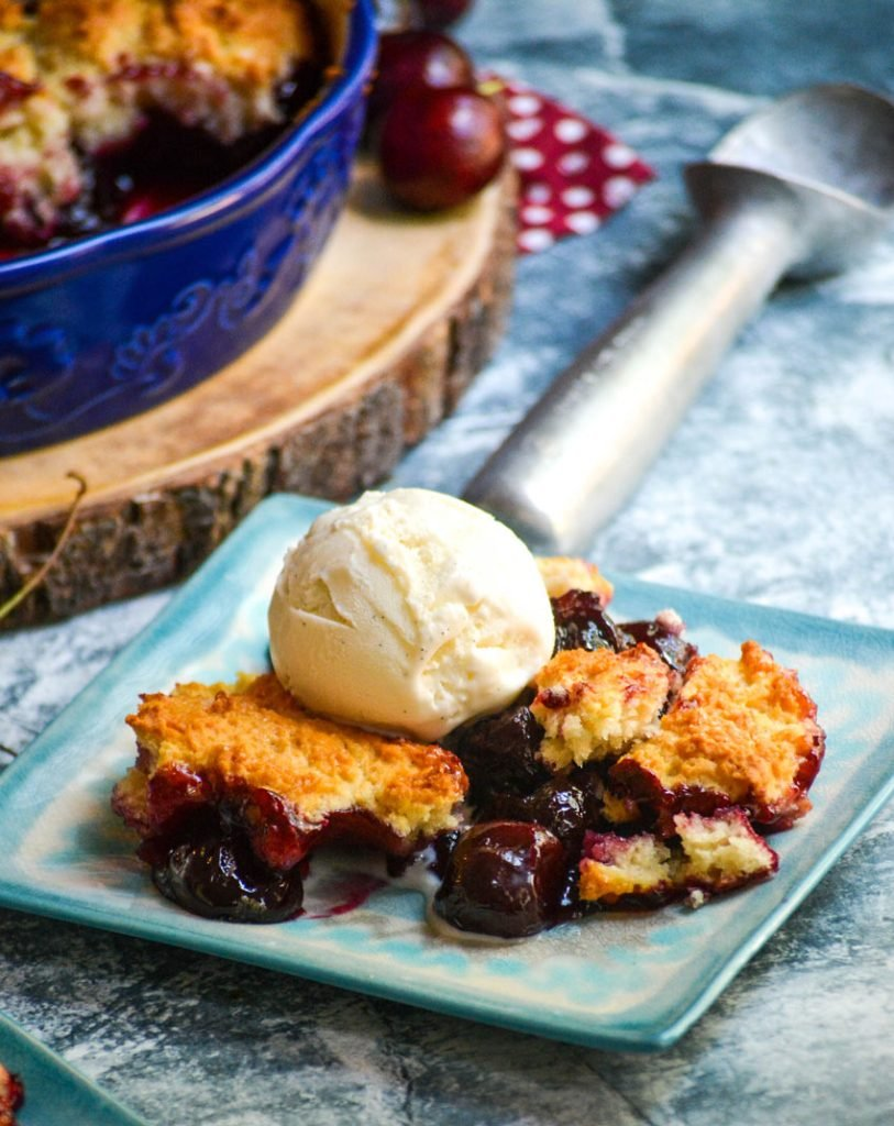 sweet cherry cobbler served on light blue plates with a scoop of vanilla ice cream