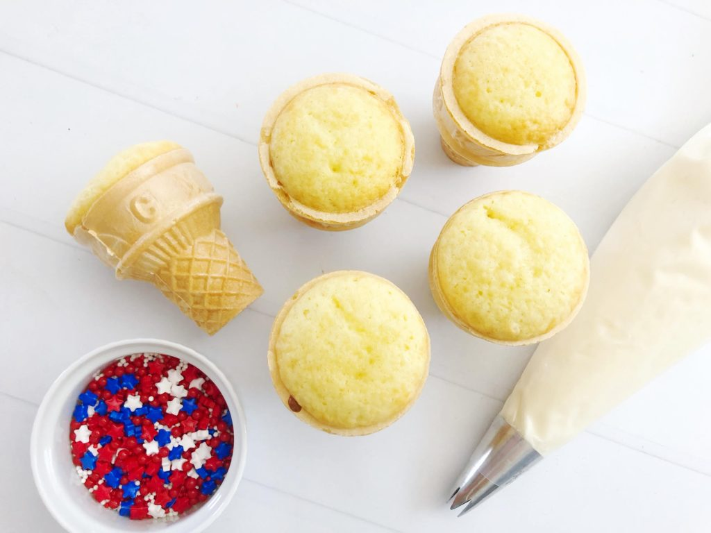 cupcakes baked into sundae cones with a white bowl filled with red white & blue sprinkles and a piping bag filled with white buttercream in the background