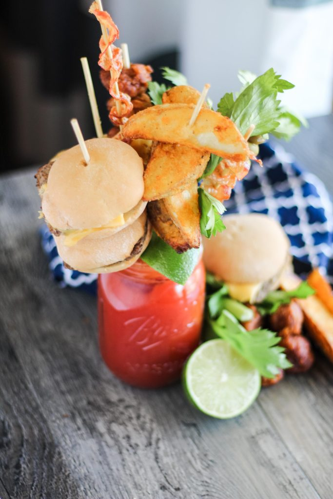 ultimate bloody mary in a Mason jar with a variety of skewered appetizers for garnish