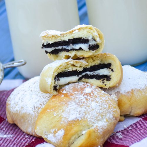 air fryer state fair style oreos on a checkered napkin with glasses of milk