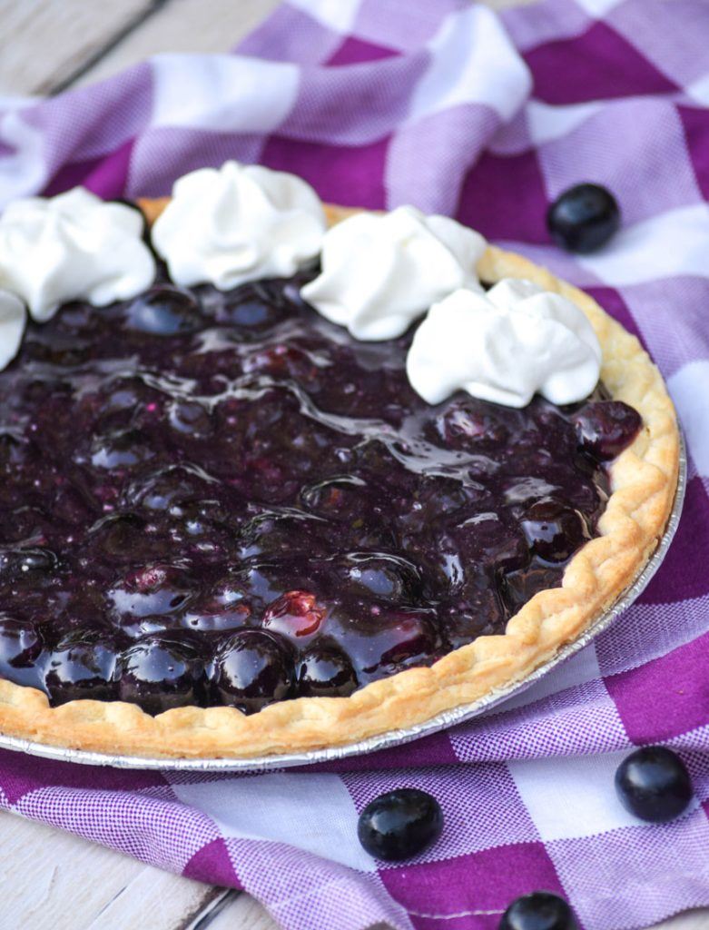 black grape pie with dollops of whipped cream on a purple checkered napkin