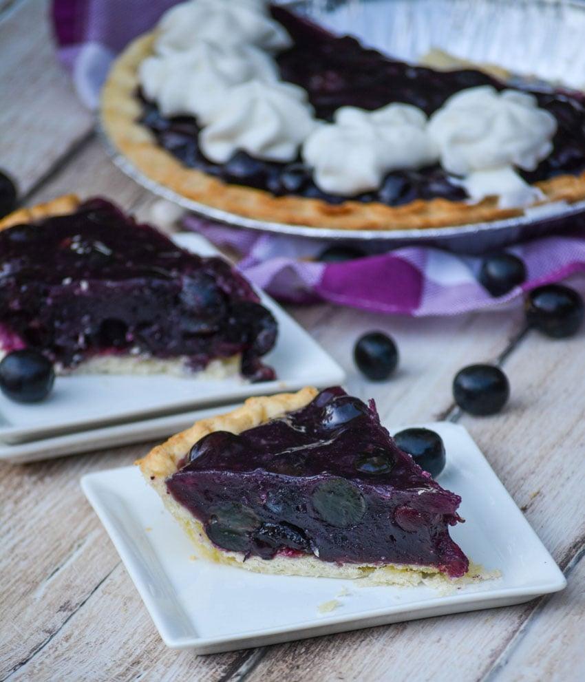 slices of black grape jello pie shown on square white appetizer plates