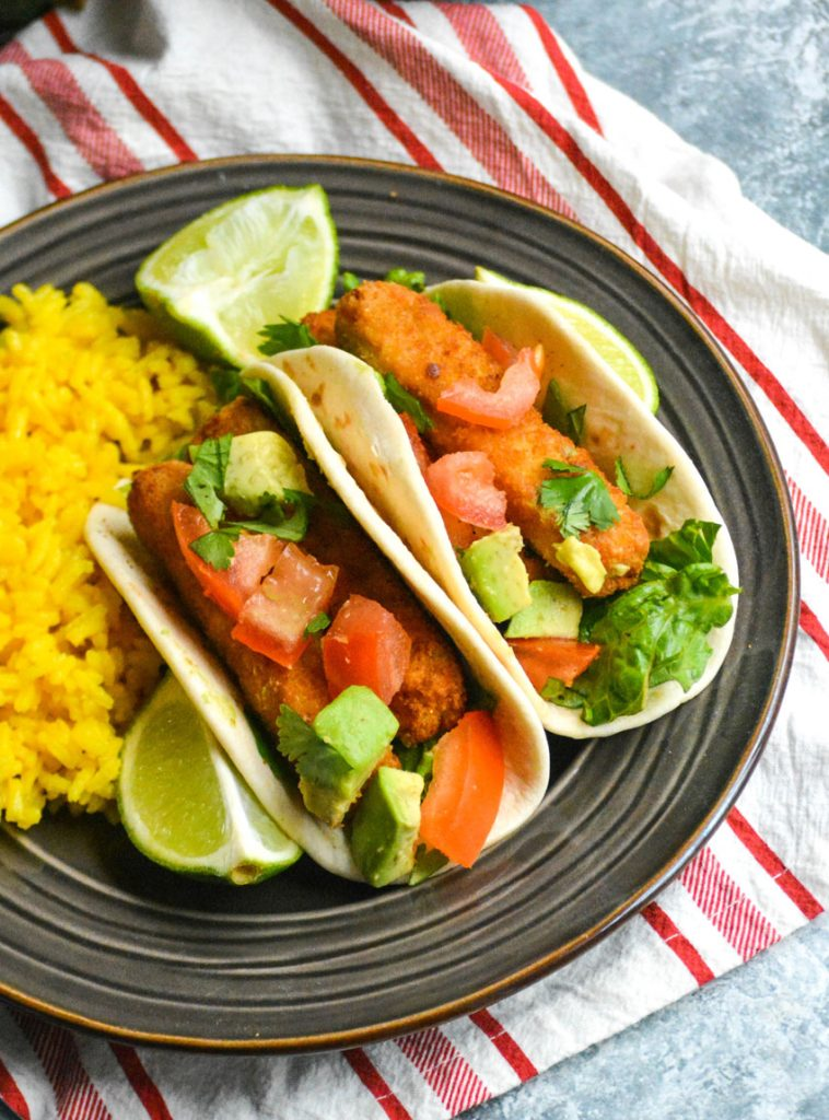 two chili lime fish stick tacos shown on a brown plate with fresh lime wedges and yellow rice