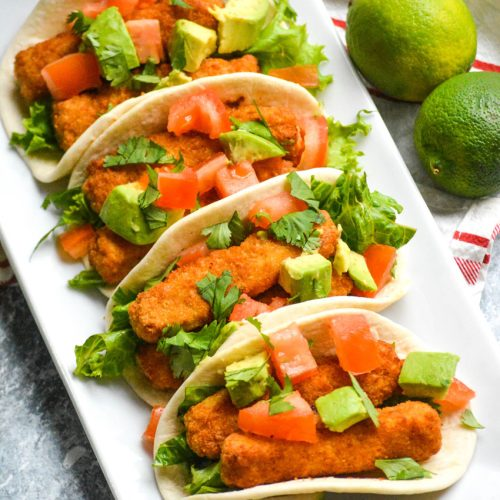 chili lime fish stick tacos in flour tortillas shown in a row on a white rectangular serving platter