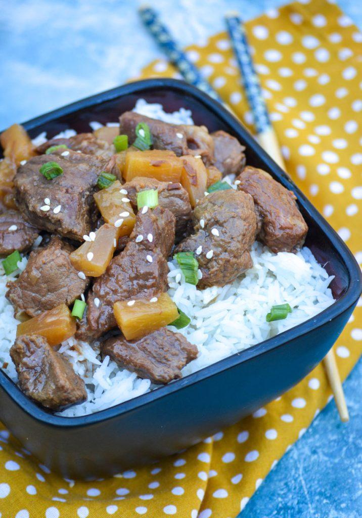 crockpot steak teriyaki served over steamed white rice in a black bowl
