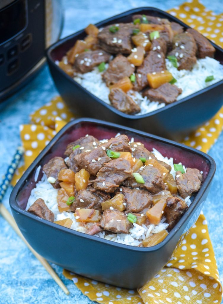 crockpot steak teriyaki served over steamed white rice in black bowls