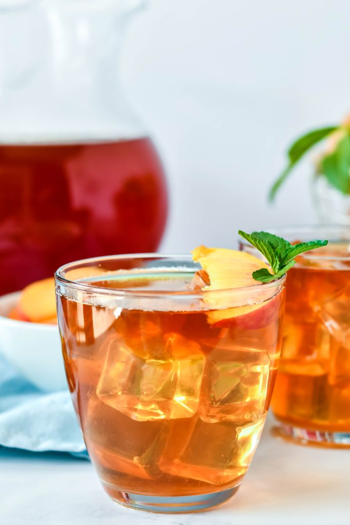 Sweet Peach Tea Recipe served in clear glasses and garnished with fresh peach slices and a sprig of mint