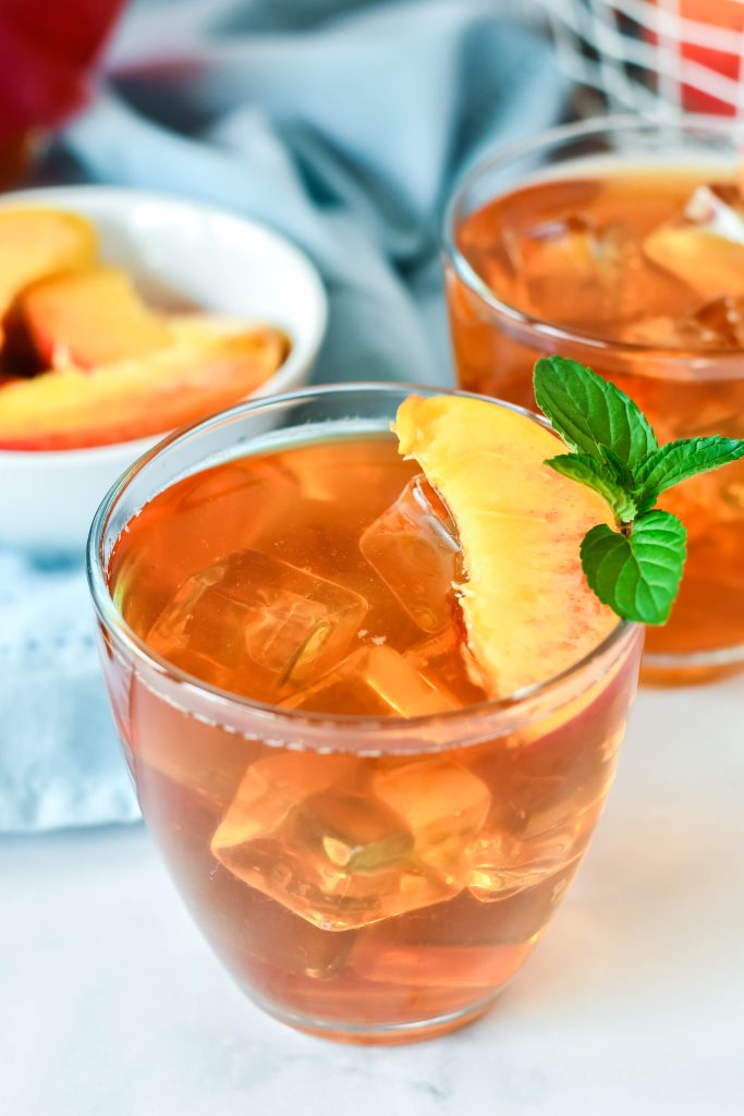 Southern sweet Peach Tea Recipe served in clear glasses and garnished with fresh peach slices and a sprig of mint