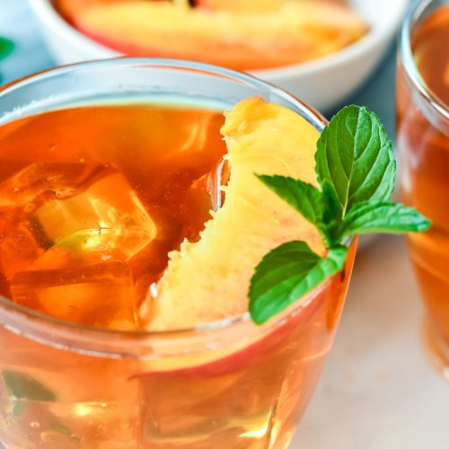 Peach Tea Recipe served in clear glasses and garnished with fresh peach slices and a sprig of mint