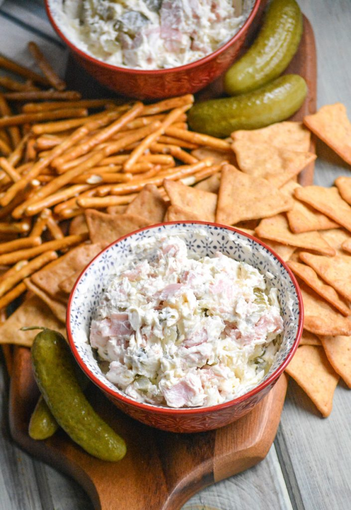 dill pickle wrap dip in a red bowl shown on a cutting board with pretzels & crackers ready to be served