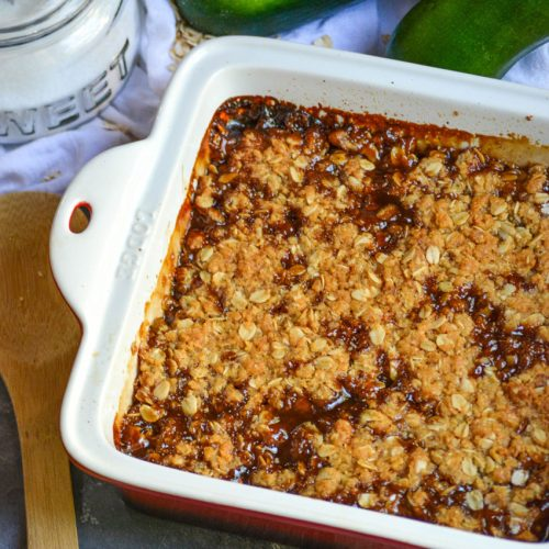 mock apple crisp in a square baking dish shown with a wooden serving spoon, sugar, and ripe zucchini in the background