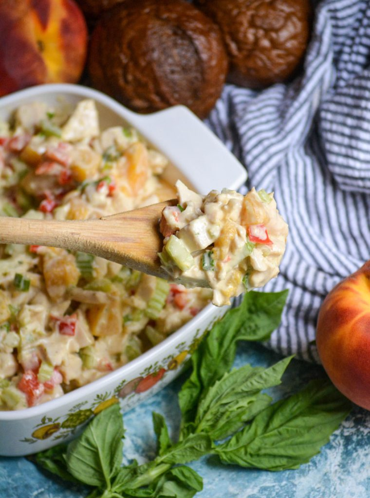 peach basil chicken salad in a white square pyrex dish with a wooden spoon