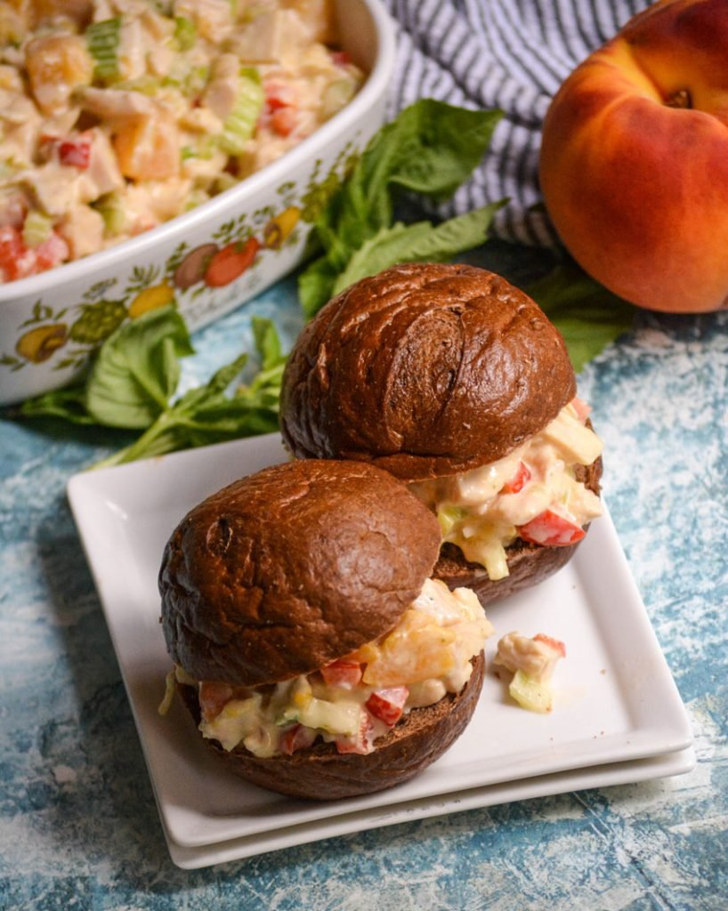 peach basil chicken salad shown on pumpernickel slider buns on a white appetizer plate