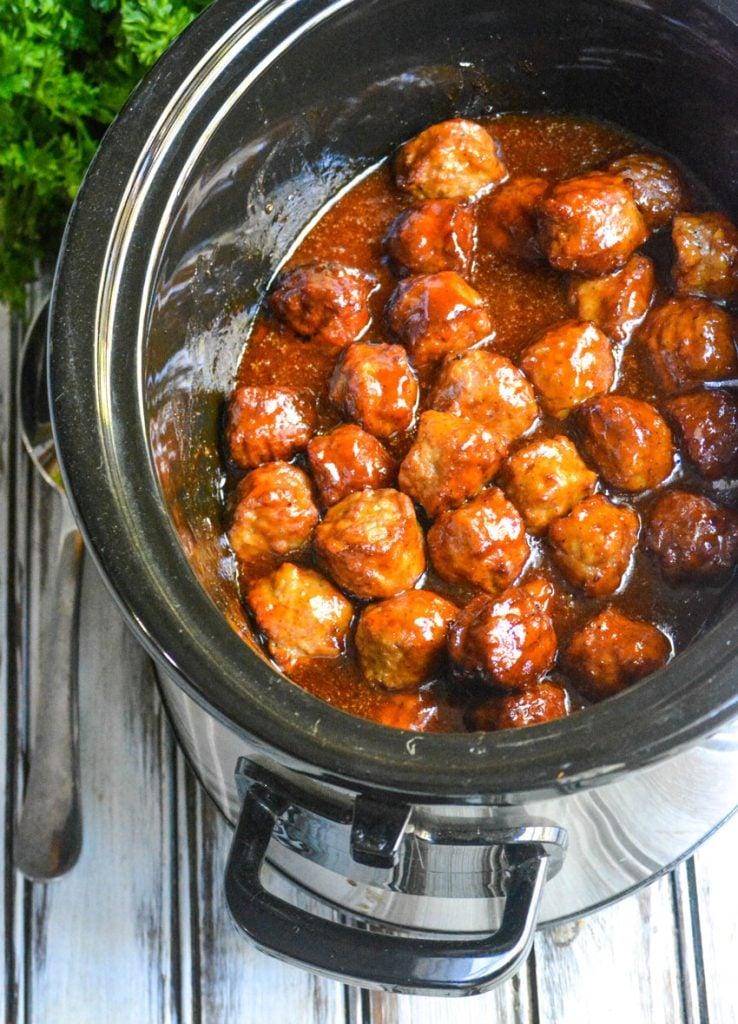 saucy peach bourbon meatballs shown in the black bowl of a crockpot