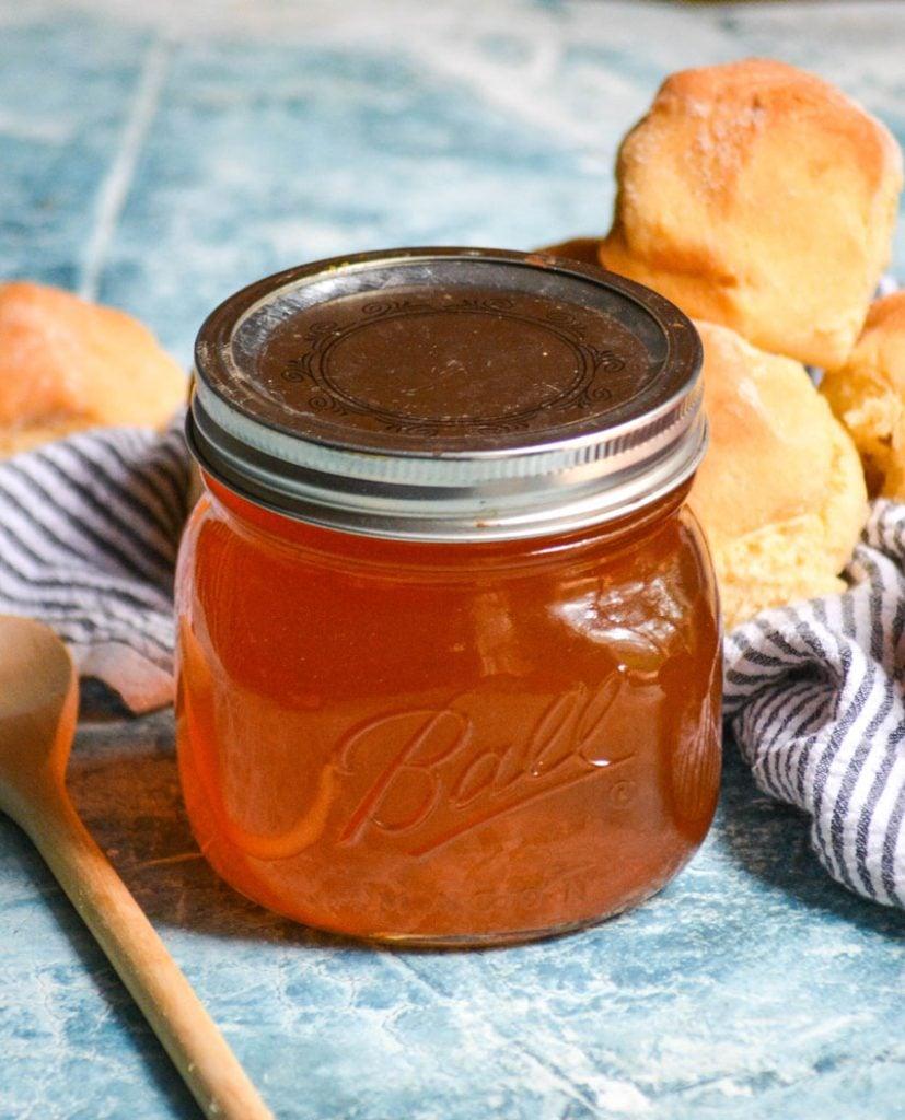 simple peach syrup shown in a sealed glass mason jar