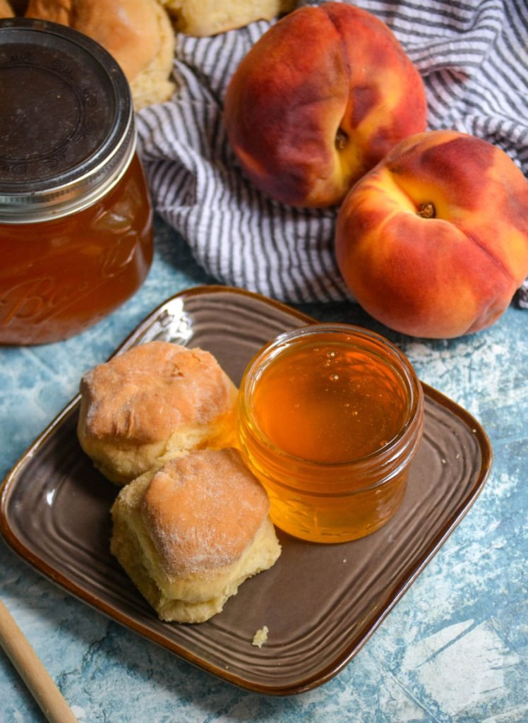 homemade peach syrup in a glass jar on a brown plate next to buttermilk biscuits