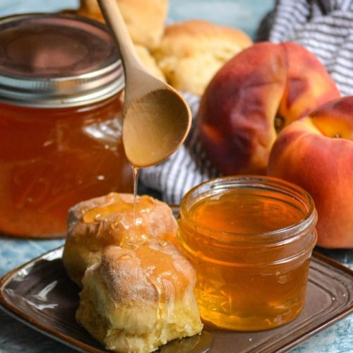 homemade peach syrup being spooned over buttermilk biscuits