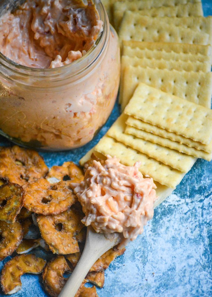 Southern style pimento cheese shown on a wooden spoon laid on top of pretzels and crackers