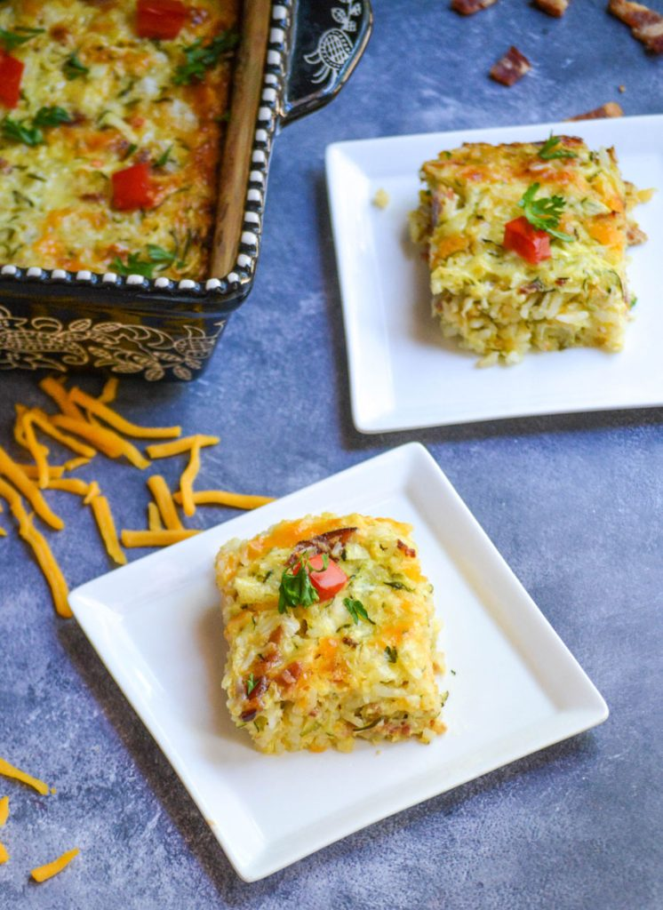 slices of Zucchini Rice Casserole with bacon on square white appetizer plates