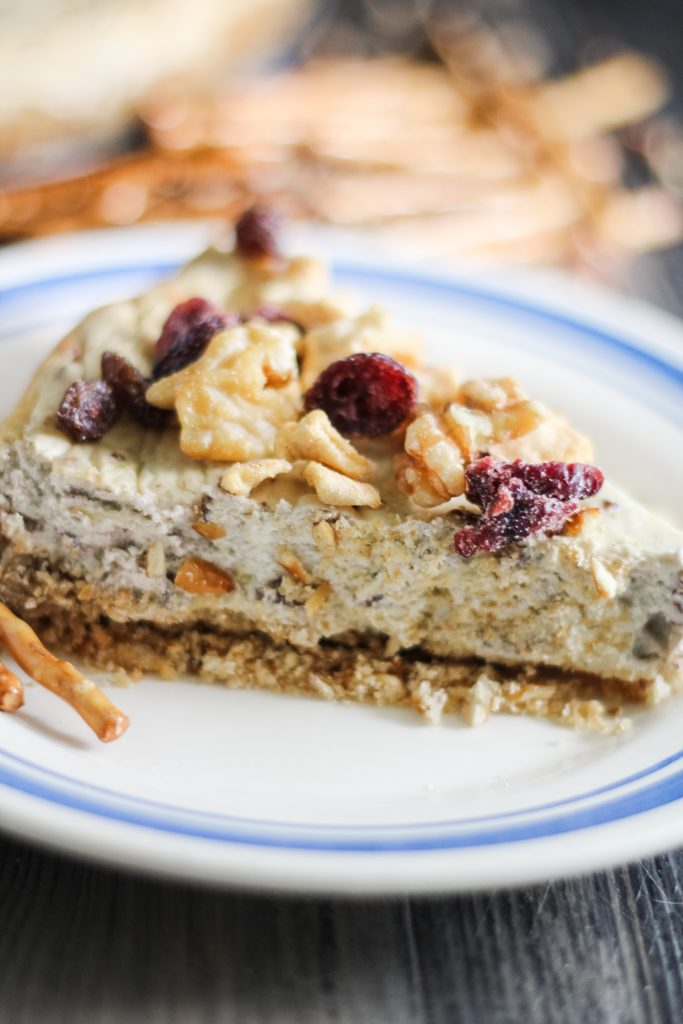savory cheesecake served on a white plate and topped with chopped pecans and dried cranberries