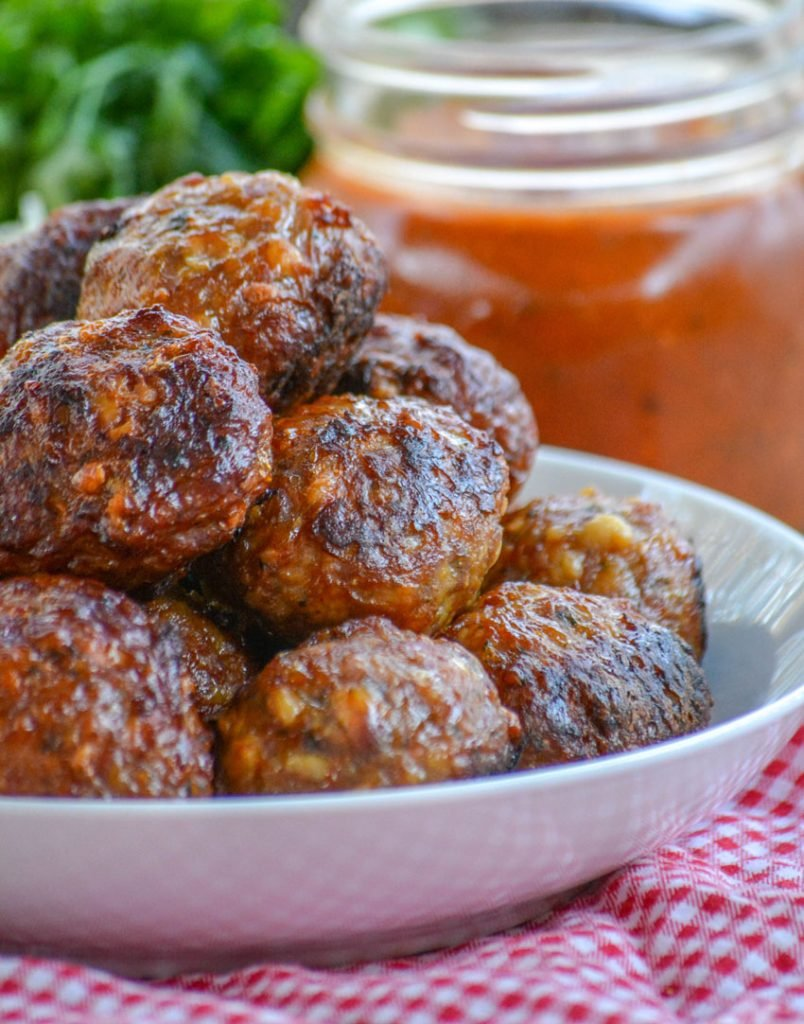 cooked homemade Italian meatballs stacked in a white bowl