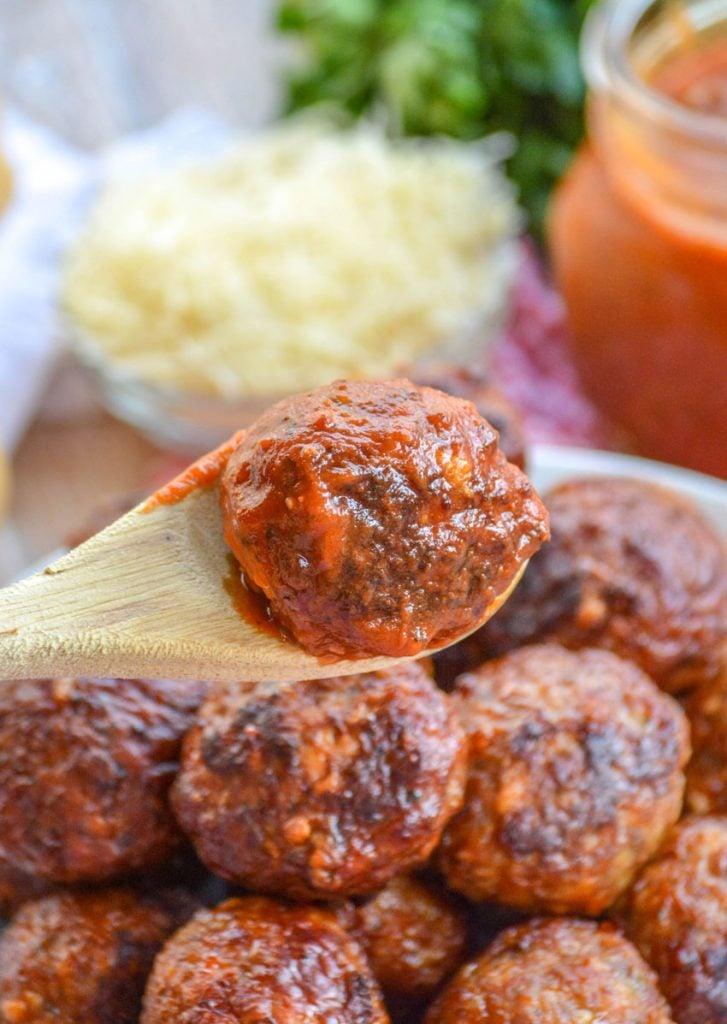 a wooden serving spoon holding aloft a sauced Italian meatball